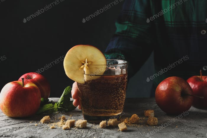 Woman hold glass of cider. Composition with cider on gray table