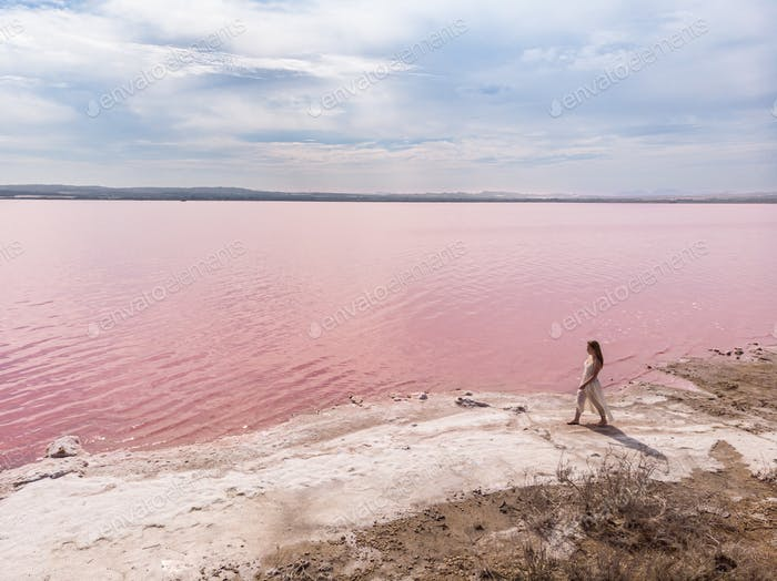 cute teenager woman wearing white dress walking on a amazing pink lake