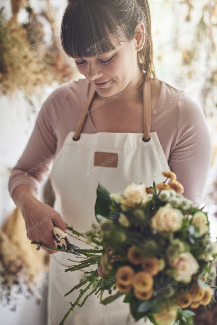 Smiling florist trimming stems on a bouquet in her shop