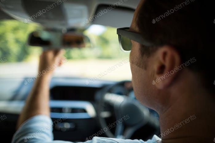 Man adjusting rearview mirror in car