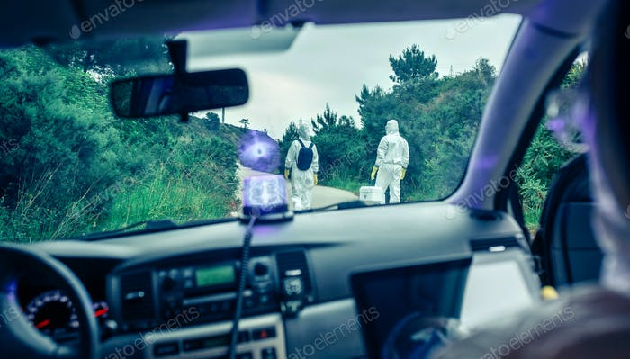 View from inside the car of people in bacteriological protection suits doing research