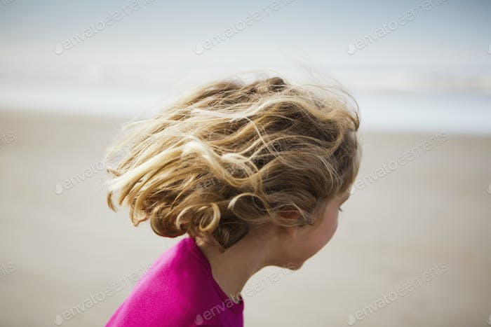 A six year old child on the beach, at Long Beach Peninsula with windblown hair.
