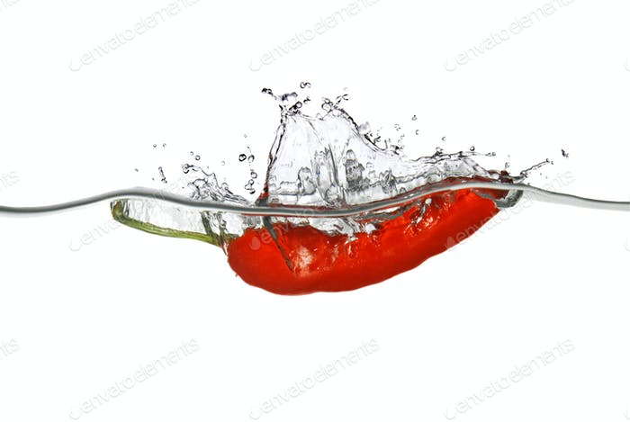 red pepper dropped into water with splash isolated on white