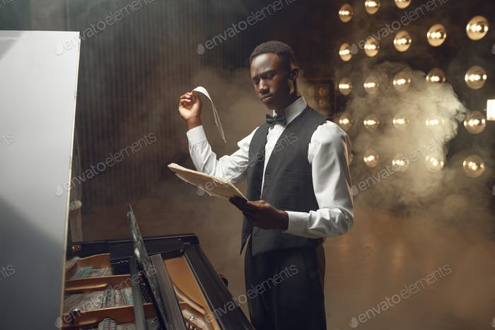 Grand piano player with music notebook in hands