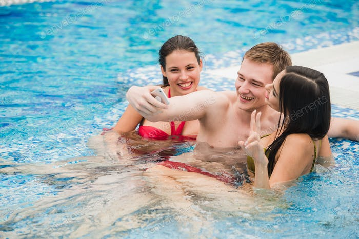 three friends taking selfie in the swimming pool. Concept about friendship, people,technology and