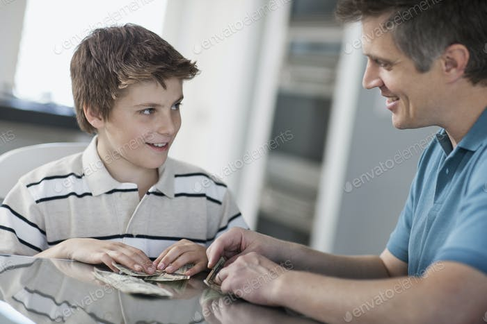 A man and a boy seated at a table, counting and handling cash.