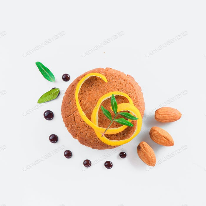 Cookie decorated with lemon zest, almond and green leaves on a white background. Pastry styling tips