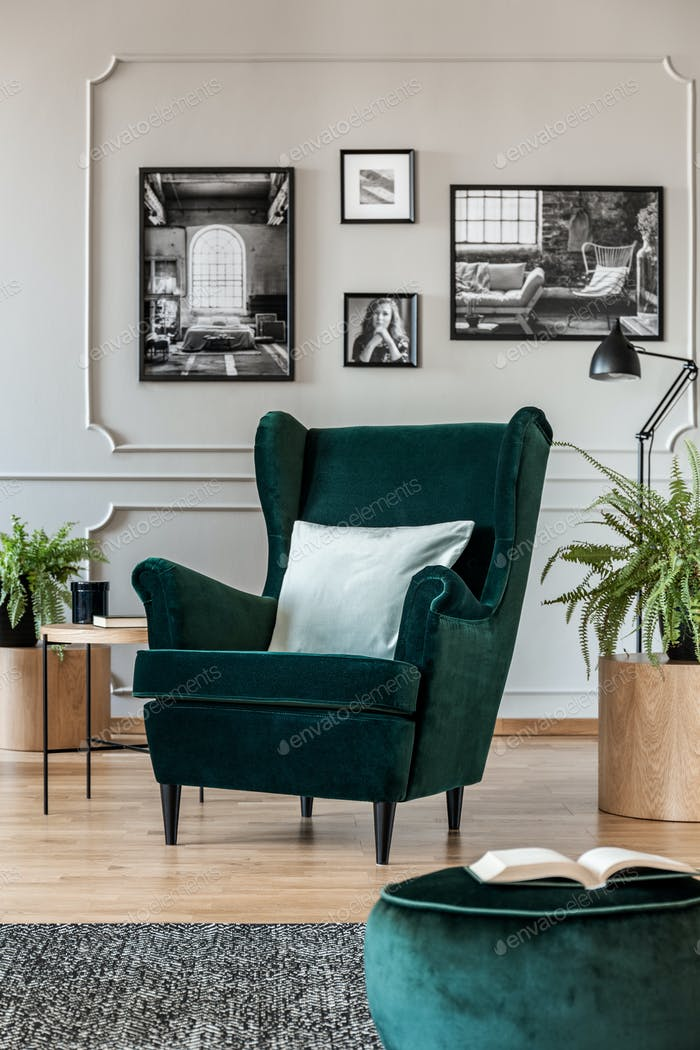 Pillow on emerald green armchair in elegant living room with bla