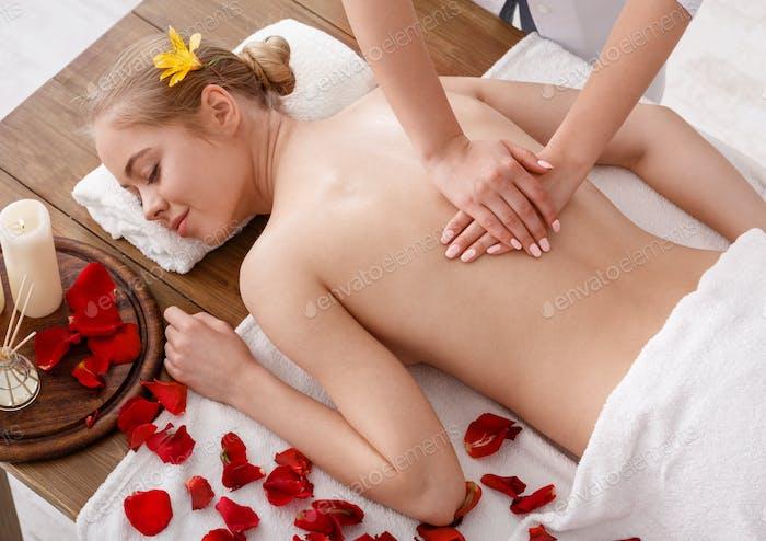 Thai-Massage im Spa. Masseur macht Verfahren für Mädchen auf dem Tisch