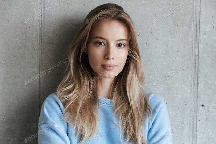 Hübsche Frau stehend über graue Wand Hintergrund