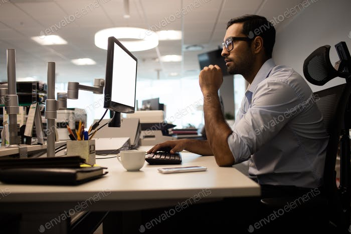 Thoughtful businessman working on computer in office