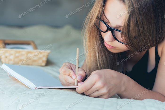Satisfied and happy smiling girl lying on sofa in room, and writing notebook