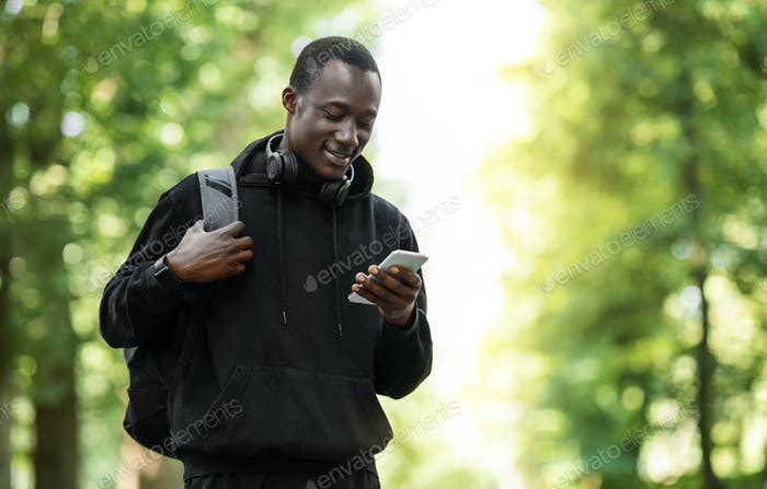 Cheerful black guy using smartphone, training at park