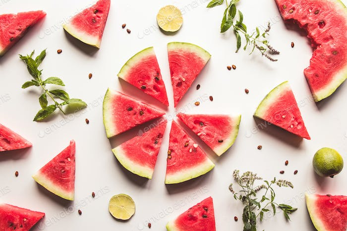 sliced watermelon on white background with lime and mint