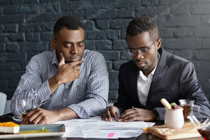 Two handsome dark-skinned executives having thoughtful and serious facial expression while reviewing