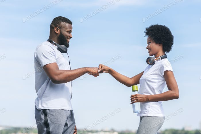 Afro Man And Woman Giving Fist Bump After Jogging Outdoor