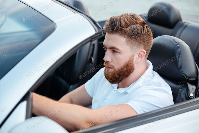 Hübscher junger bärtiger Mann fährt sein Auto