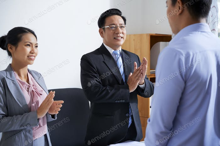 Business people applauding coworker