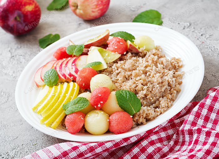 Healthy breakfast. Buckwheat or porridge with fresh melon, watermelon, apple and pear. Tasty food.