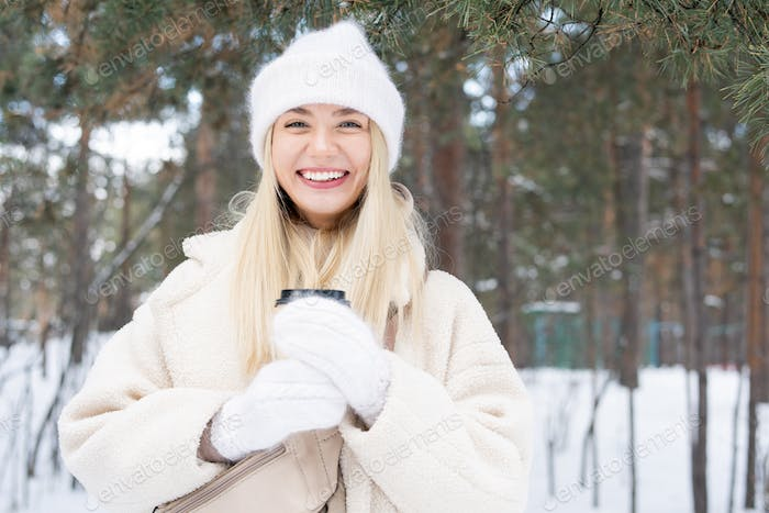 Happy young laughing blond female looking at you in snowbound forest