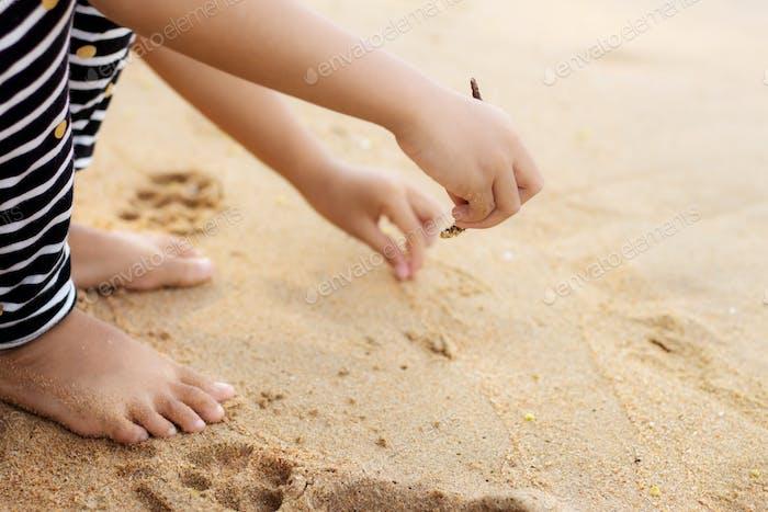 Girl on sand and writing