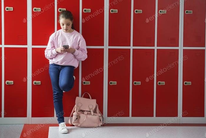 Schoolgirl using smartphone at school