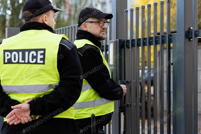 Two policemen stand in front of the entrance gate to the house during home intervention