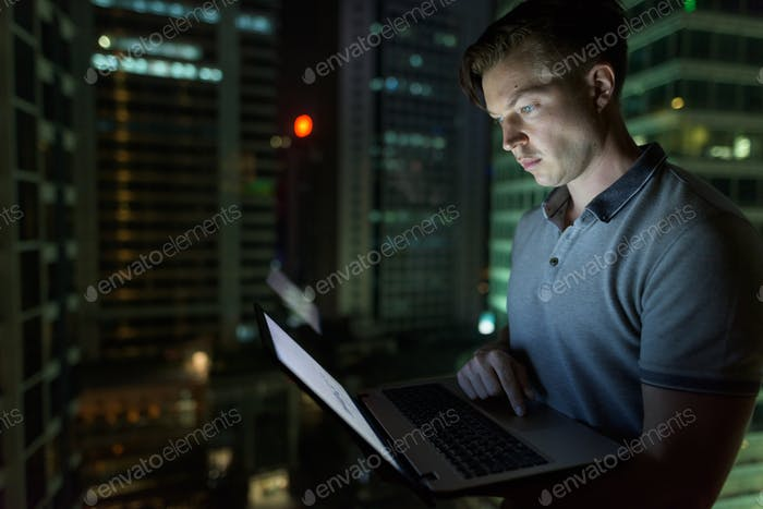 Young handsome man using laptop against glass window with view o