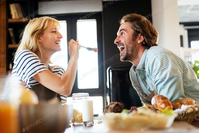 Wife in love feeding her husband and having fun in kitchen