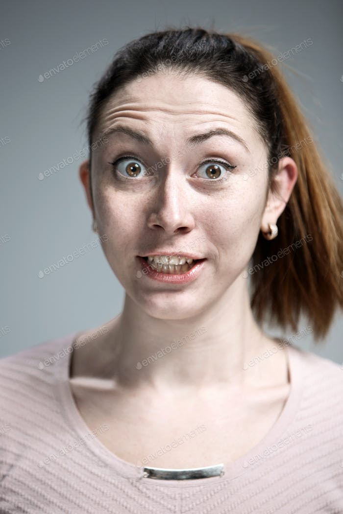 Portrait of young woman with shocked facial expression