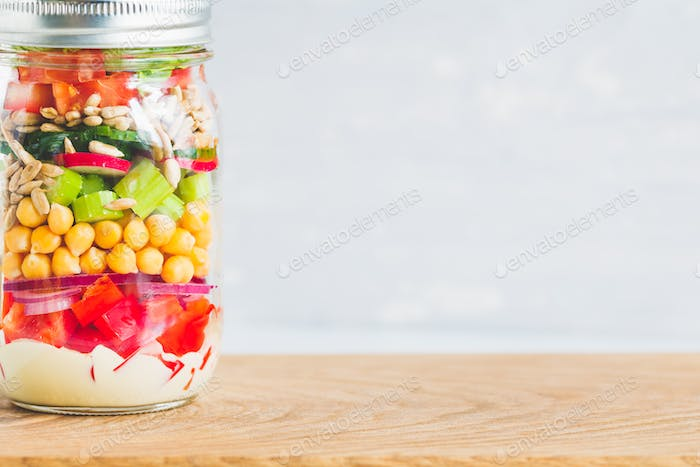 Single jar with layering vegan salad for healthy lunch