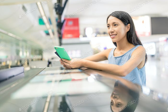 Woman waiting for check in and using mobile phone in the counter