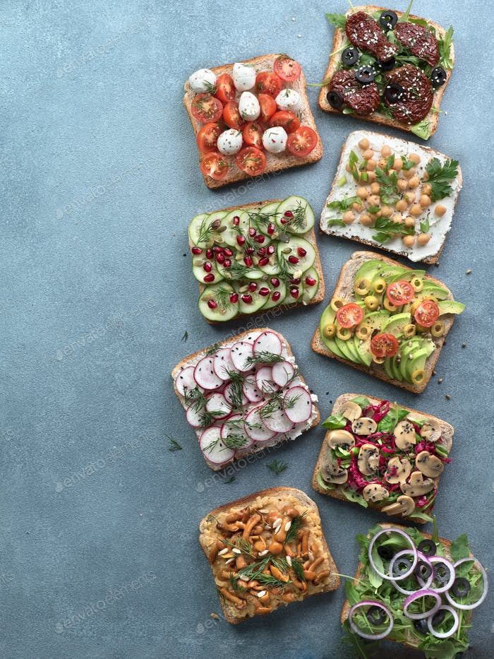 Assortment vegan sandwiches on gray stone background