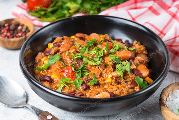 Chili con carne from meat and vegetables on stone table close up