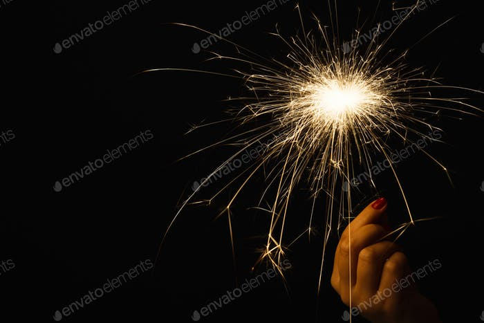 New year party sparkler in female hand on black background