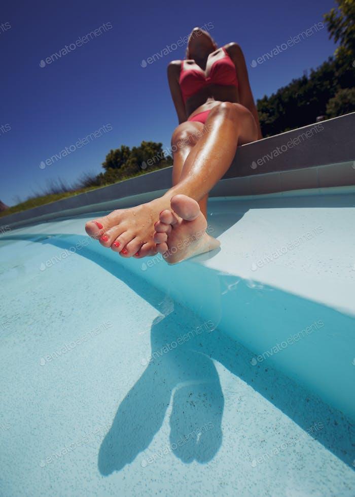 Young lady in bikini sunbathing by poolside