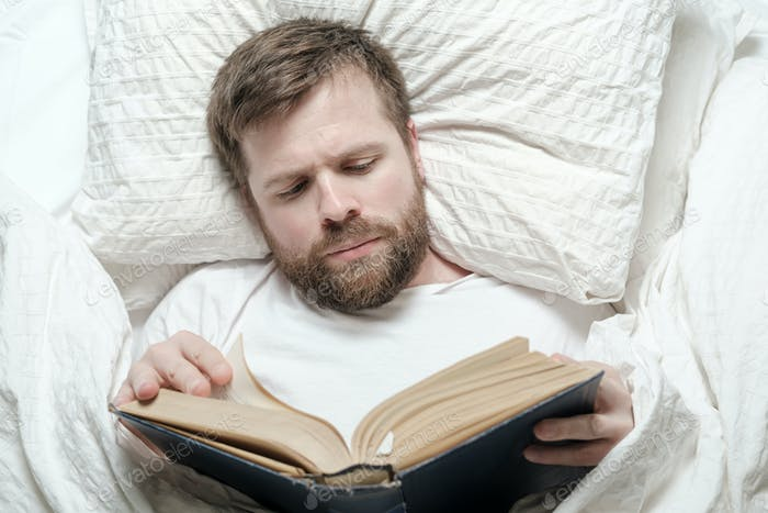 Attractive bearded man reading a book while lying in bed. Education concept. Top view.