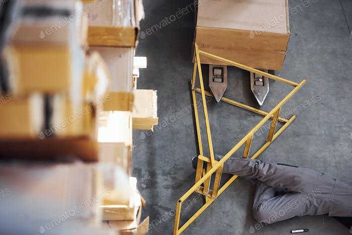 Lagerarbeiter nach einem Unfall im Lager. Mann in Uniform liegend auf dem Boden