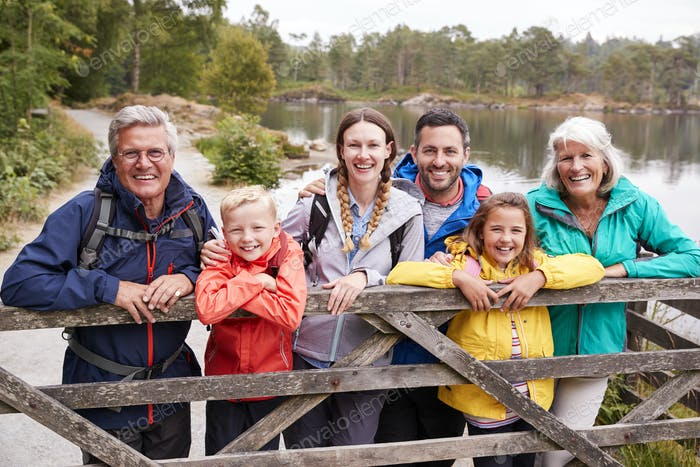Multi generation family standing behind a wooden fence looking to camera, Lake District, UK