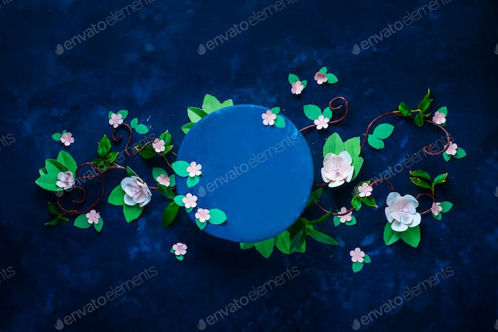 Blooming apple tree branch with a circle template. Dark blue background flat lay with copy space