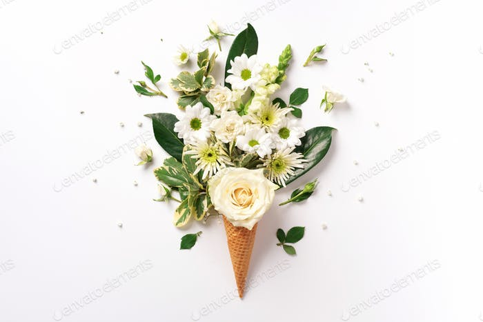Summer minimal concept. Ice cream cone with white flowers and leaves on light background. Flat lay