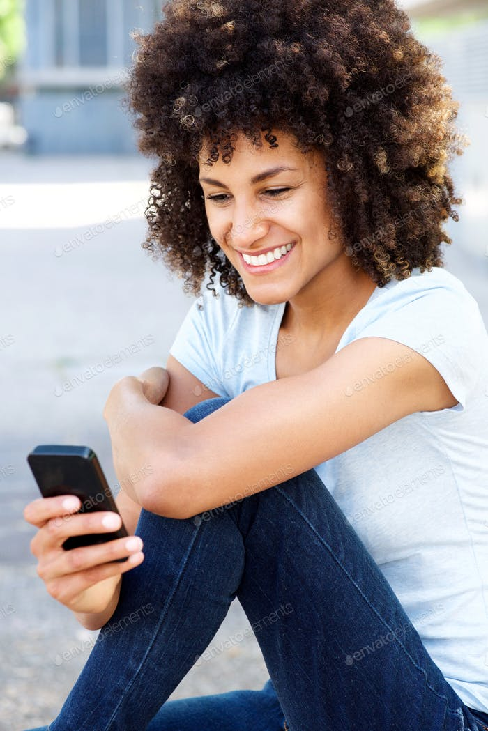 Smiling woman sitting outside holding mobile phone