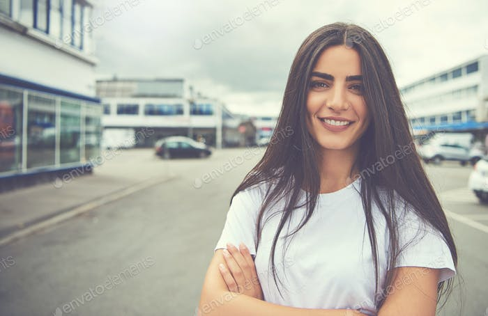 Happy woman with folded arms standing outside
