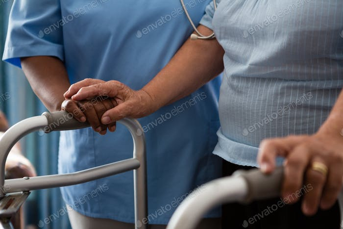Nurse assisting senior patient in walking with walker at nursing home