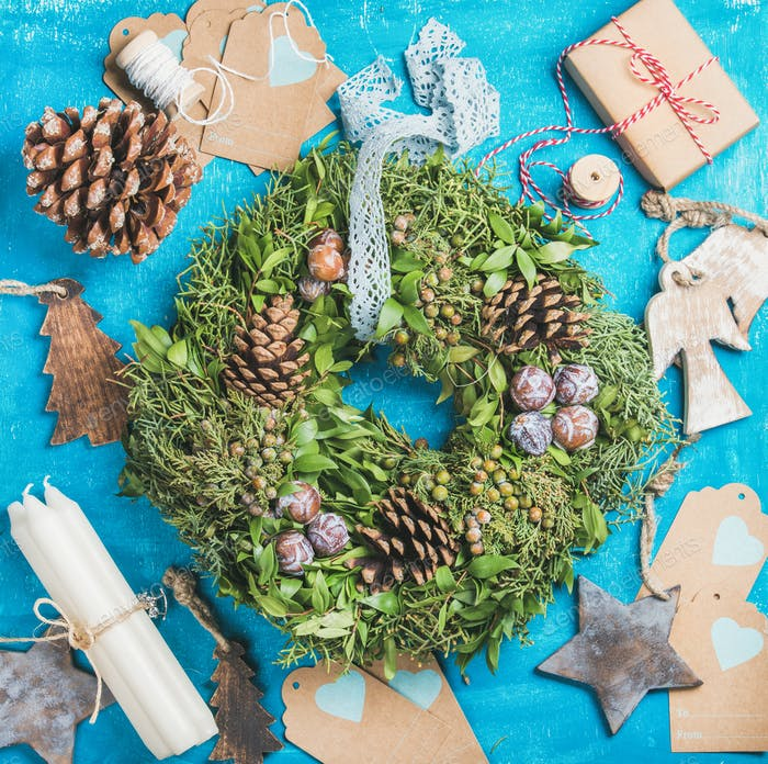 Christmas wreath, pine cones, toys, decorative materials over blue background