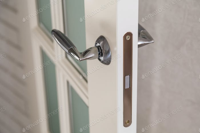 Wooden door with contemporary magnetic latch on modern interior.