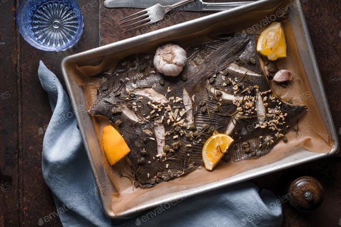 Baking tray with flounder and seasoning on the stone background top view