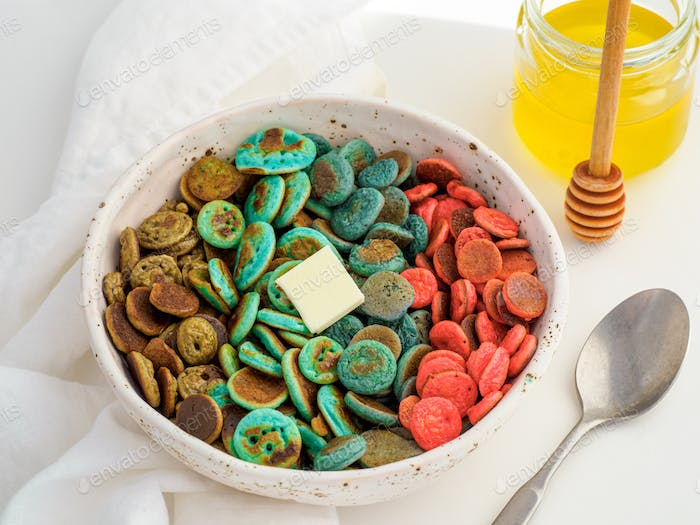 Colorful pancake cereal in baby hands