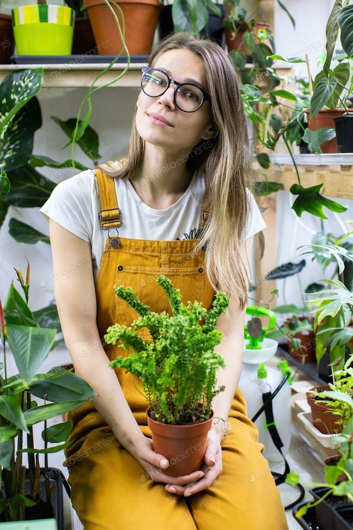 Woman gardener in glassesholding a fern in plastic pot. Home gardening, love of houseplants, hobbie.