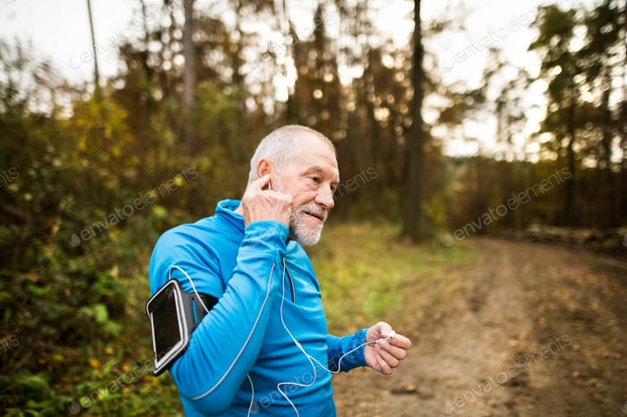 Senior runner in nature with smart phone and earphones.